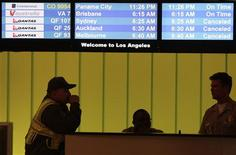 <p>Electronic screens display cancelled Qantas Airline flights as security officers look on at Los Angeles International Airport in California, October 29, 2011. Qantas said on Sunday it had cancelled 447 flights affecting more than 68,000 passengers since grounding more than 100 aircraft around the world on Saturday. REUTERS/Jason Redmond</p>