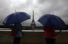 <p>Tourists protect themselves from the rain under umbrellas in front of the Eiffel tower as they visit the French capital during summer holidays in Paris July 19, 2011. REUTERS/Eric Gaillard</p>