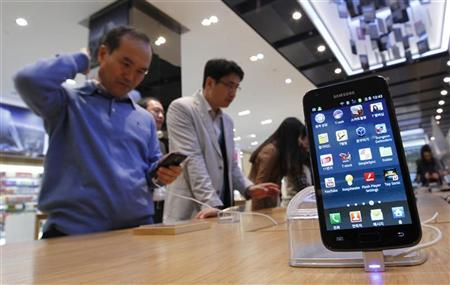 Customers look at Samsung Electronics' Galaxy S II LTE smartphones on display at a shop at the company's headquarters in Seoul October 28, 2011. Samsung Electronics Co overtook Apple Inc as the world's top smartphone maker in the July-September period with a 44 percent jump in shipments, and forecast strong sales in the current quarter in a clear warning to its rivals. REUTERS/Jo Yong-Hak (SOUTH KOREA - Tags: BUSINESS)