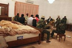 <p>Libyan fighters speak to a member of the National Transitional Council (NTC) in a room in Muammar Gaddafi's villa just outside Obari November 3, 2011. REUTERS/Oliver Holmes</p>