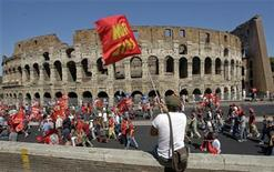 <p>A demonstrator waves a flag in front of the Colosseum during a demonstration in Rome, September 6, 2011. REUTERS/Remo Casilli</p>
