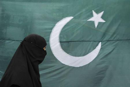 A woman clad in a burqa walks past the national flag of Pakistan in Lahore August 13, 2011. REUTERS/Mohsin Raza/Files