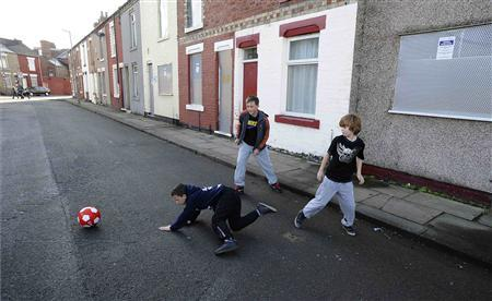 Boys play football on Kingston Street in Middlesbrough, November 6, 2011. REUTERS/Nigel Roddis