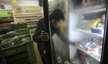 A man takes out a packet of yogurt from a refrigerator at a food store in Noida, November 24, 2011. REUTERS/Parivartan Sharma