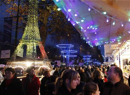 Shoppers visit the Christmas market along the Champs Elysees in Paris, December 3, 2011. At left is a model of the Eiffel Tower. REUTERS/Mal Langsdon