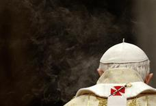<p>Pope Benedict XVI is surrounded by the smoke of an incense burner as he leads the Christmas mass in Saint Peter's Basilica at the Vatican December 25, 2011. REUTERS/Max Rossi</p>