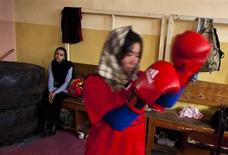 <p>A visitor (L) watches as an Afghan woman practises inside a boxing club in Kabul December 28, 2011. Female boxing is still relatively unusual in most countries, but especially in Afghanistan, where many girls and women still face a struggle to secure an education or work, and activists say violence and abuse at home is common. Many in this conservative society still consider fighting taboo for women, and the country's first team of female boxers deal with serious threats. Picture taken December 28, 2011. REUTERS/Ahmad Masood</p>