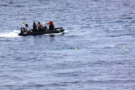 Activists from the Sea Shepherd Conservation Society aboard a rubber boat deploy a buoy-fitted rope aiming to disable the rudder and propeller of Japanese Research vessel Yushin Maru No. 3 in the Antarctic, in this handout photo taken on January 6, 2012, released by the Institute of Cetacean Research (ICR) to Reuters on January 7, 2012. REUTERS/The Institute of Cetacean Research/Handout
