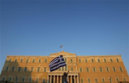 A woman raises a Greek flag during a rally against austerity in front of the parliament at Constitution (Syntagma) square in Athens June 30, 2011. REUTERS/John Kolesidis