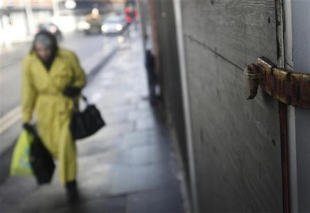 A woman walks past closed retail units in Manchester, northern England December 7, 2011. REUTERS/Danish Siddiqui