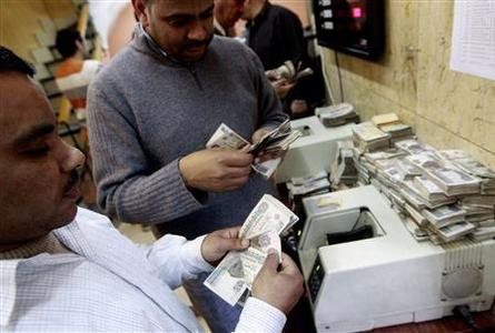 Men count Egyptian bank notes at a foreign exchange office in the centre of Cairo in this March 1, 2011 file photo. REUTERS/Peter Andrews/Files