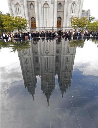 People sit by a reflecting pool outside the Salt Lake Mormon temple as they wait in line to attend the fifth session of the 181st Semiannual General Conference of the Church of Jesus Christ of Latter-day Saints in Salt Lake City, Utah, October 2, 2011. REUTERS/George Frey