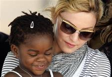<p>Pop star Madonna sits with her adopted Malawian child Mercy James during a bricklaying ceremony at the site of her Raising Malawi Girls Academy, near the capital Lilongwe in this April 6, 2010 file photo. REUTERS/Mike Hutchings/Files</p>