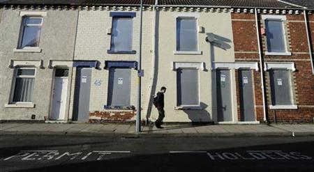 A pedestrian walks past boarded up houses on Coral Street in Middlesbrough, northern England November 6, 2011. REUTERS/Nigel Roddis