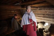 <p>Students Maarja Lainevoog (L) and Kristin Otti warm themselves inside an Iron Age viking log house replica in Rouge February 1, 2012. REUTERS/Ints Kalnins</p>