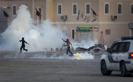 An anti government protester threatens to throw a molotov cocktail at police firing tear gas from their cars in Sitra, southeast of Manama, January 26, 2012. REUTERS/Caren Firouz