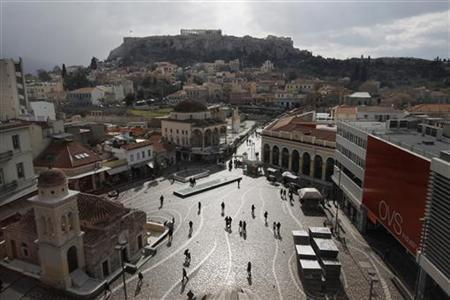 People walk on the Monastiraki square as the Acropolis hill is seen in the background in central Athens January 31, 2012. REUTERS/John Kolesidis