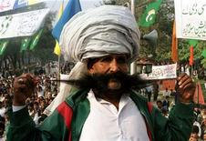 <p>Ellahi Bakhsh Baluch, a Pakistani renowned for his thick mustache, poses on a stage during a nationl flag rally in Islamabad November 30 1998. REUTERS/Stringer .</p>