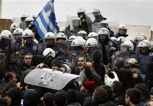 <p>Anti-austerity protesters carry a police shield during scuffles in front of the parliament in Athens February 7, 2012. REUTERS/Yannis Behrakis</p>