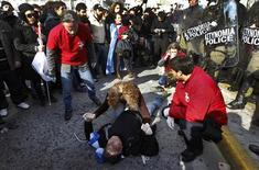 <p>Medics try to help an anti-austerity protester, who lies unconscious after he was injured by police, in front of the parliament in Athens February 11, 2012, during a demonstration on the second day of a 48-hour strike by Greek workers unions. REUTERS/Yannis Behrakis</p>