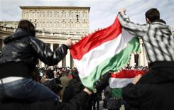 <p>Pilgrims wave Hungarian flags as Pope Benedict XVI leads the Sunday angelus prayer in Saint Peter square at the Vatican February 12, 2012. Pope Benedict urged the Syrian government on Sunday to recognise the legitimate aspirations of its people and embark on a national dialogue to put an end to a violent crackdown on protesters which has killed thousands since March. REUTERS/Tony Gentile</p>