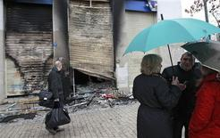 <p>Devant un magasin incendié dimanche en Grèce, où des violences ont éclaté alors que le parlement votait un nouveau plan d'austérité pour satisfaire aux exigences de ses bailleurs de fonds internationaux. /Photo prise le 13 février 2012/REUTERS/John Kolesidis</p>