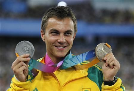 Bronze medalist L.J. van Zyl of South Africa holds his medal after the men's 400 meters hurdles event together with his silver medal for the men's 4x400 meters relay at the IAAF World Championships in Daegu September 3, 2011. REUTERS/Lee Jae-Won