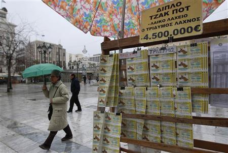 A woman walks past a lottery seller post during a rainy day in Athens February 16, 2012. REUTERS/Yiorgos Karahalis