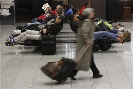 Passengers rest on chairs at the main terminal of Frankfurt's airport February 21, 2012. REUTERS/Alex Domanski
