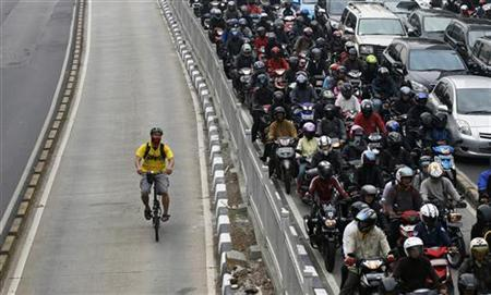 A man rides a bicycle in a bus lane next to a morning rush hour traffic jam in Jakarta November 10, 2011. REUTERS/Supri