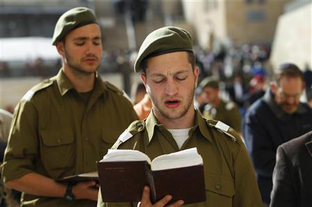Israeli soldiers pray at the Western Wall, Judaism's holiest prayer site, in Jerusalem's Old City February 22, 2012. The Israeli Defence Force (IDF) has always been a 'Jewish' army. Its rations are kosher, its chaplains are rabbis, and it operates - with the exception of wartime - around the festival calendar. It has never drafted soldiers from Israel's 20-percent Arab minority. But its Jewish identity has always been more cultural than religious. IDF personnel data suggests that's changing. Around 57 percent of Israel's Jewish majority, census figures show, define themselves as religiously observant to some degree. Two relatively small but distinct groups of religious Israelis are growing both in numbers and in power in the military: the ascetic, often apolitical and ultra-pious 'haredim', who join up despite their community's exemption from conscription; and pro-settlement Orthodox Jews, whose dogma focuses less on religious rite and more on the sanctity of Israel's fight for territorial expansion. REUTERS/Baz Ratner