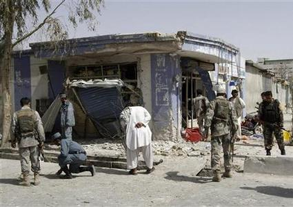 Afghan police investigate at the site of a motorcycle bomb attack in Kandahar province March 14, 2012. REUTERS/ Ahmad Nadeem