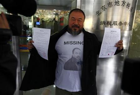 Dissident Chinese artist Ai Weiwei opens his coat to reveal a shirt bearing his portrait as he holds his tax bond agreement slips while leaving the Beijing government tax bureau November 16, 2011. REUTERS/David Gray