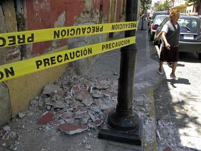 A resident evades rubble after an earthquake, in Oaxaca March 20, 2012. The U.S. Geological Survey said the quake was 7.6 on the Richter scale and located the epicenter of the quake at Oaxaca State. REUTERS/Jorge Luis Plata