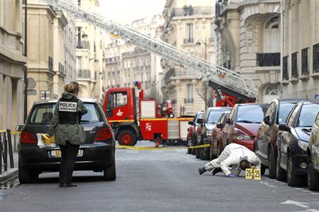Police search the street for clues near the Indonesian embassy where a package bomb exploded in Paris March 21, 2012. REUTERS/Benoit Tessier