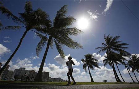 A woman jogs along a path in Ala Moana Park in Honolulu, Hawaii November 8, 2011. REUTERS/Jim Young