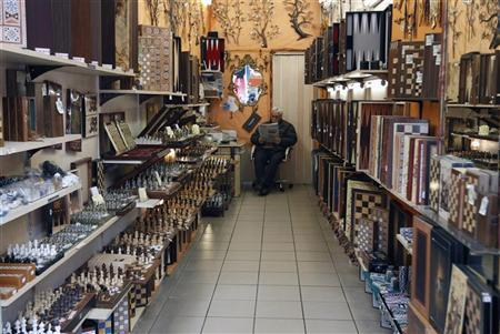 A man reads a newspaper in an empty souvenir shop at Monastiraki tourist area in Athens February 8, 2012. REUTERS/John Kolesidis