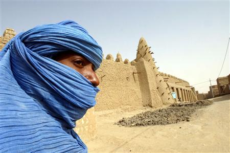 A Tuareg nomad stands near a 13th century mosque in Timbuktu in this March 19, 2004 file photo. REUTERS/Luc Gnago/Files