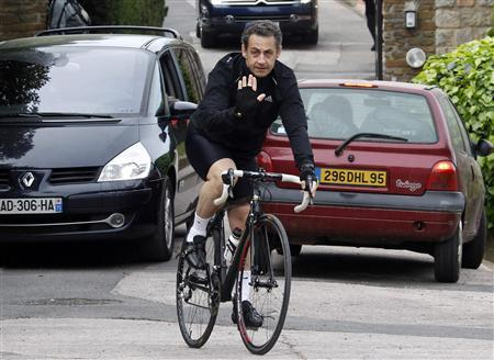 France's President and UMP candidate for the 2012 French presidential election Nicolas Sarkozy waves as he cycles away from the home of First Lady Carla Bruni-Sarkozy in Cavaliere, southern France, April 9, 2012. REUTERS/Jean-Paul Pelissier