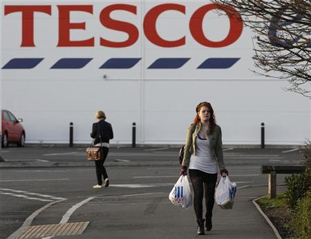 A shopper leaves a Tesco store in Loughborough, central England January 12, 2012. REUTERS/Darren Staples