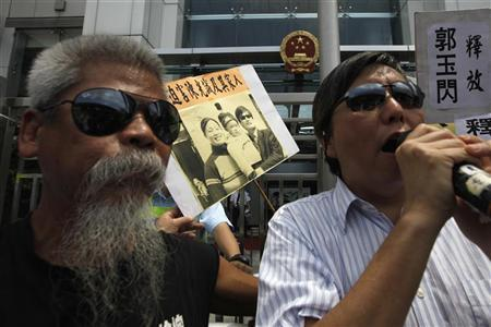 Protesters, wearing sunglasses, shout slogans in support of Chinese dissident Chen Guangcheng outside the Chinese liaison office in Hong Kong April 30, 2012. REUTERS/Tyrone Siu