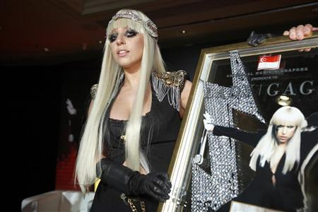 U.S. singer Lady GaGa poses with a plaque presented to her by Universal Music Group during a media event for the launch of Singtel's AMPed music service in Singapore June 14, 2009. REUTERS/Tim Chong
