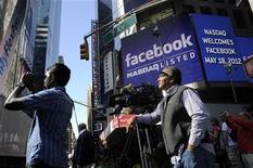 """<p>A New York lors du premier jour de cotation de Facebook sur le Nasdaq. Des actionnaires du réseau social ont intenté une action en justice pour dissimulation d'informations au cours du processus de mise sur le marché. Ils estiment qu'on leur a caché """"une réduction grave et prononcée"""" des prévisions de croissance du chiffre d'affaires de Facebook, dont l'action a perdu près de 18% de sa valeur depuis son introduction. /Photo prise le 18 mai 2012/REUTERS/Keith Bedford</p>"""