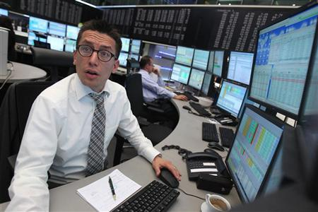 A trader reacts at his desk in front of the DAX board at the Frankfurt stock exchange May 7, 2012. REUTERS/Alex Domanski