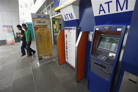 People walk past ATM machines at a shopping centre in Yangon May 27, 2012. REUTERS/Soe Zeya Tun