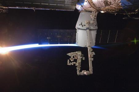 With the Earth's horizon as a backdrop, the SpaceX Dragon commercial cargo craft is seen berthed to the International Space Station, May 25, 2012. REUTERS/NASA