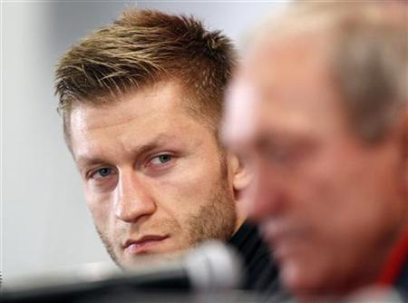 Jakub Blaszczykowski (L), captain of Poland's National team looks at head coach Franciszek Smuda during a news conference at the National Stadium in Warsaw February 28, 2012. REUTERS/Peter Andrews