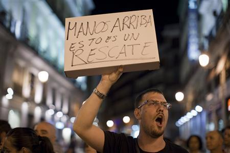 A protester holds up a sign, which reads: ''Hands up, this is a rescue'', in reference to Spain's bailout, in Puerta del Sol square in Madrid, June 9, 2012. REUTERS/Paul Hanna