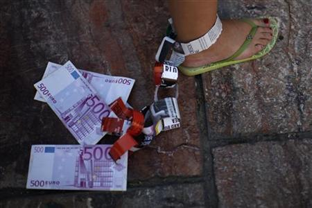 A demonstrator hangs fake Euro notes on her leg during a protest against Spain's bailout at La Constitucion square in Malaga, southern Spain, June 10, 2012. REUTERS/Jon Nazca