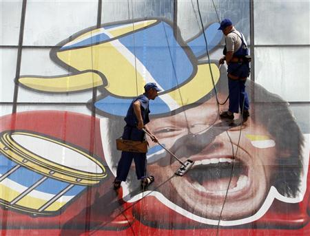 Workers clean the windows of a shopping centre, displaying a Euro 2012-themed decoration above a fan zone which will be used to screen soccer matches, in Kiev May 31, 2012. REUTERS/Anatolii Stepanov